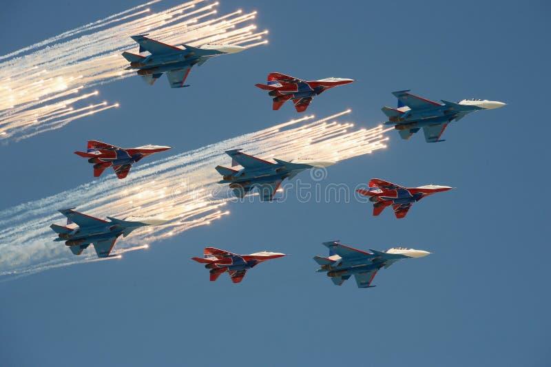 Aerobatic ` su-30cm och MiG-29 för ` för flygplan för ` för lag`-Swifts ` och för ` rysk riddaregjorde honnören under en repetiti arkivfoto