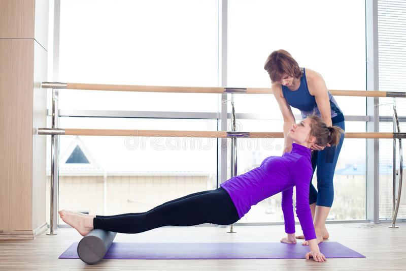 Aerobics Pilates personal trainer helping women stock photos