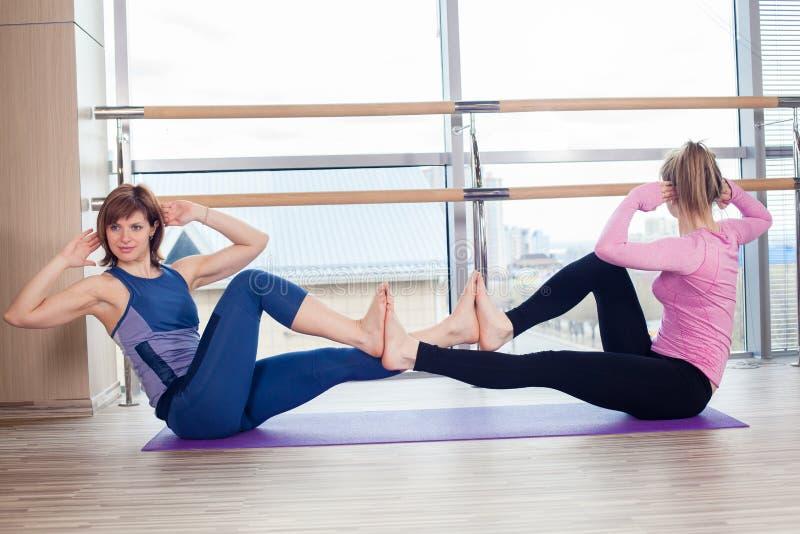 Aerobics Pilates personal trainer helping women royalty free stock image