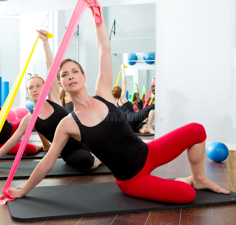 Aerobics pilates women with rubber bands in a row royalty free stock images