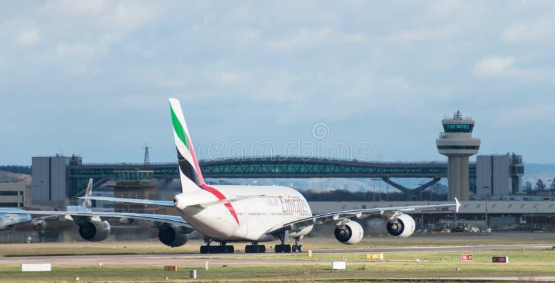 Aerobus A380 emirat linii lotniczej taxi po lądować przy Londyńskiego Gatwick lotniskiem z kontrola lotów wierza w tle zdjęcia royalty free