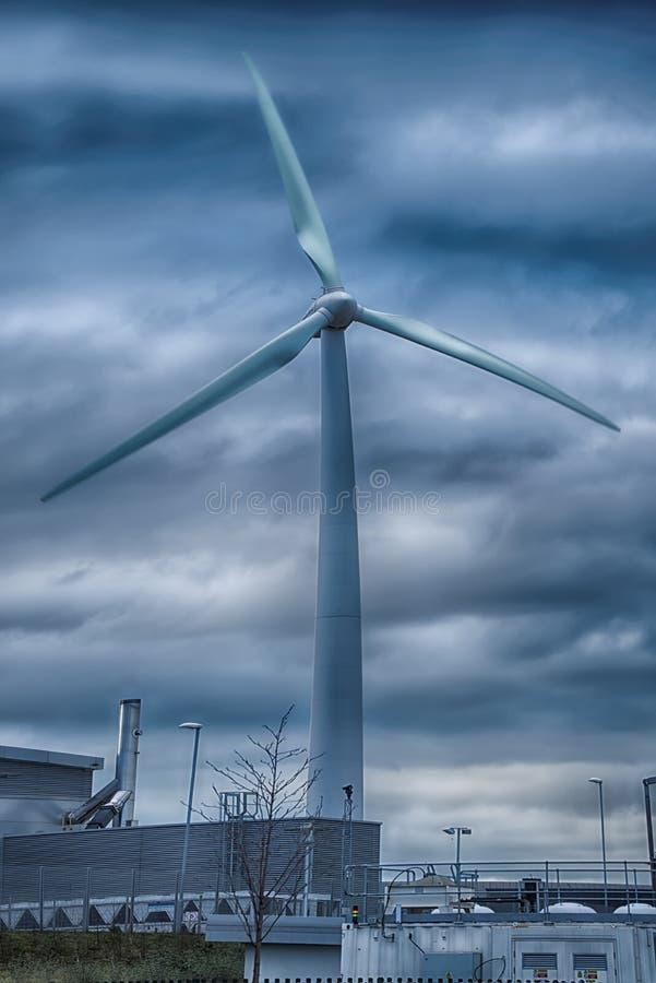 Aerogeneratorväderkvarnen mot molnig himmel arkivbild