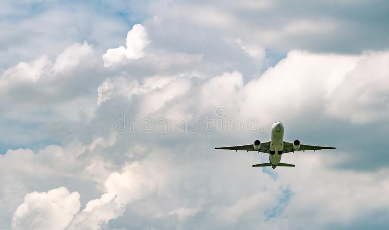 Aerolíneas comerciales que vuelan en cielo azul y nubes blanquecinas En vista de los vuelos aéreos Avión de pasajeros después del foto de archivo