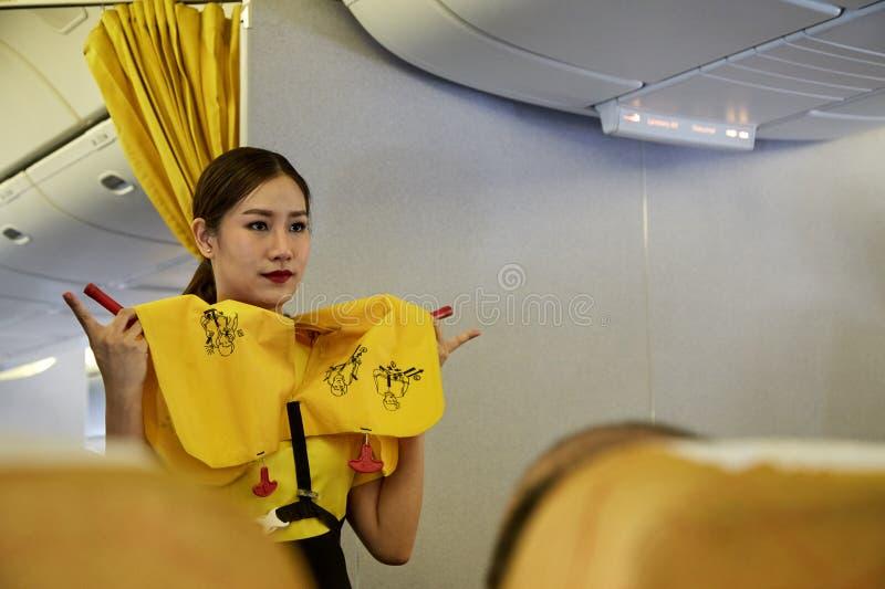 A aeromoça de ar demonstra procedimentos de segurança imagens de stock