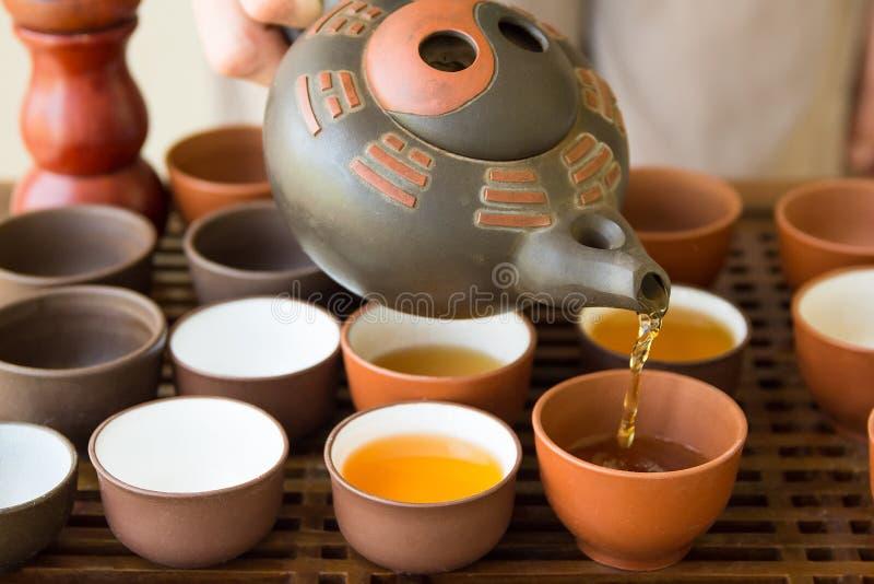Aeromoça Pouring Tea do mestre do chá da mulher no copo do potenciômetro na cerimônia Japonês chinês ajustado na bandeja de madei imagens de stock