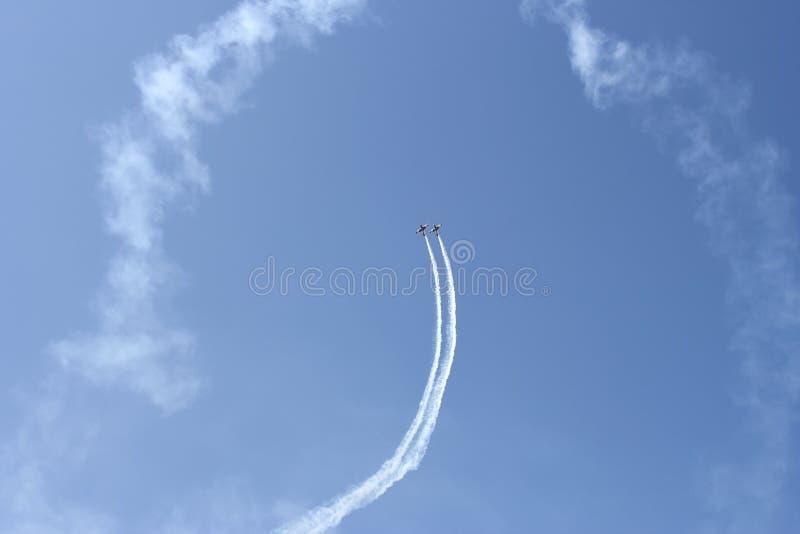 Aeronautic show. Two planes executing acrobatic fly at aeronautic show royalty free stock photos
