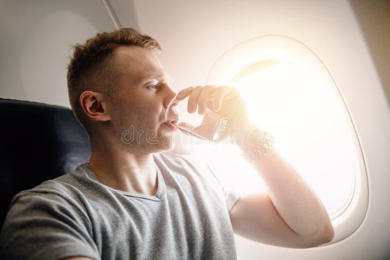 Aerophobia del concepto Asustado del miedo que vuela en un aeroplano y en la altura Agua de la bebida fotos de archivo libres de regalías