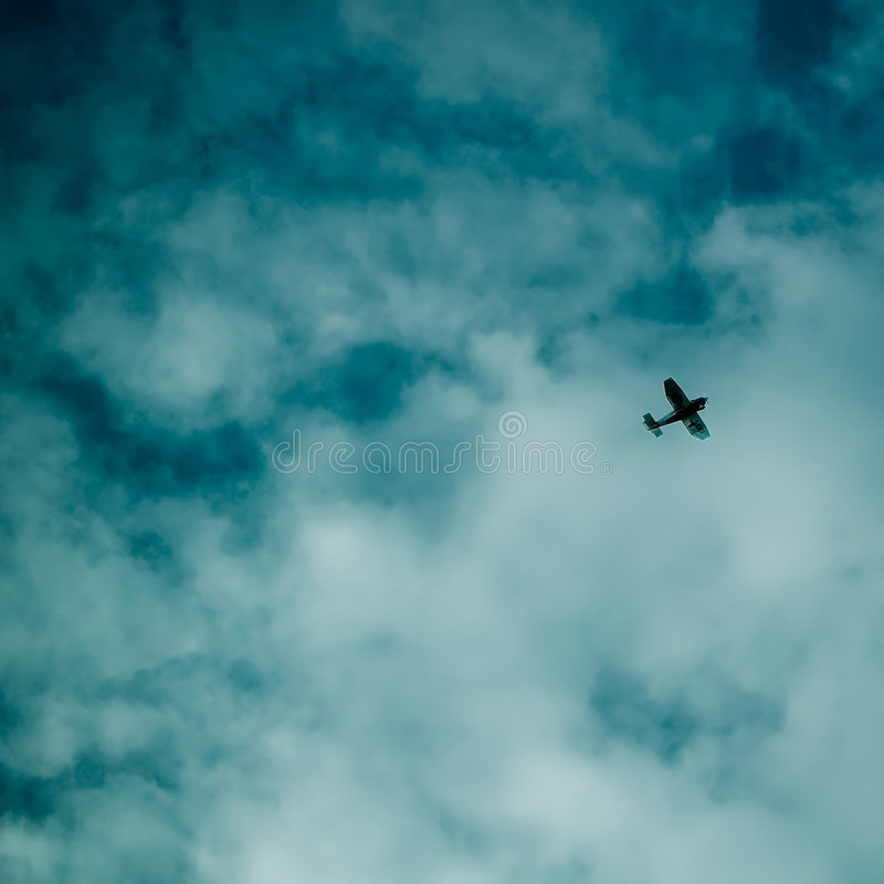 Aeroplane. Flying between clouds in the blue sky royalty free stock photo