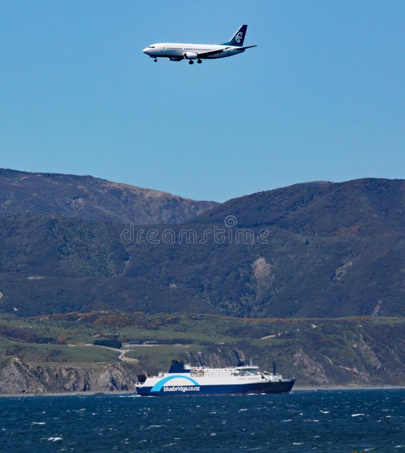 Aeroplane on final approach to Wellington airport, passes over an Interislander ferry on it`s way to South Island on the Cook stock images