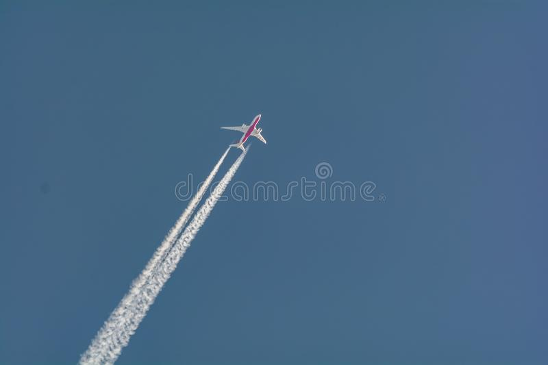 Aeroplane flight on a Blue Sky against clouds. An Aeroplane flying past the white clouds leaving a trail royalty free stock photos