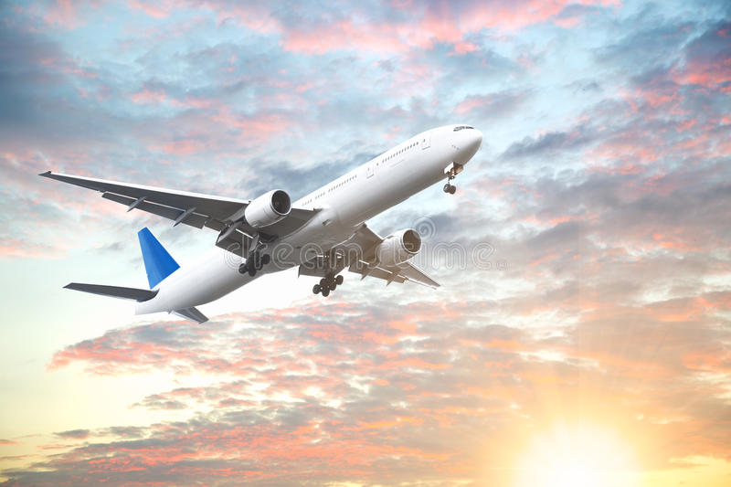 Aeroplane flying in sunset sky with beautiful cloud royalty free stock images