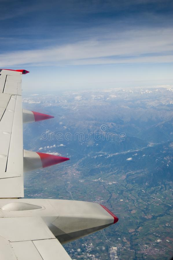 An aeroplane wing from the air with view of earth below and deep blue sky stock photography