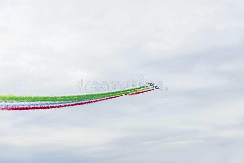Aeroplani su airshow con le tracce di fumo luminose variopinte contro un cielo blu, nuvole Aerei, esposizione volante e immagini stock libere da diritti