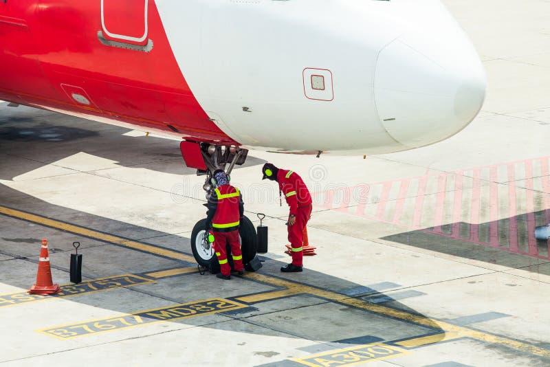 Aeroplano in aeroporto assistito dalla squadra a terra fotografia stock libera da diritti