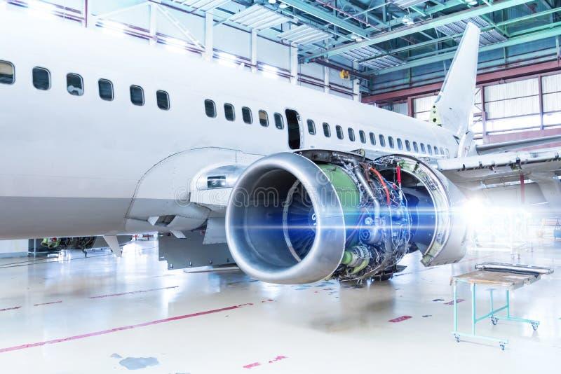 Aeroplano bianco del passeggero nell'ambito di manutenzione nel capannone Riparazione del motore di aerei sull'ala e sul controll fotografie stock libere da diritti