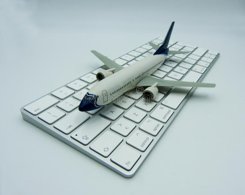 Aeroplano bianco su una tastiera di computer bianca Concetto di aviazione fotografia stock