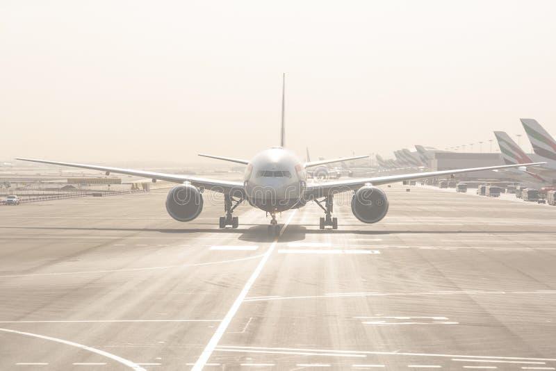 Aeroplano che decolla sulle piste internazionali dell'aeroporto del Dubai immagini stock libere da diritti