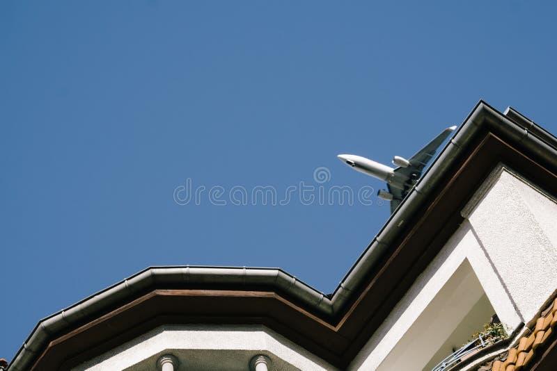 Aeroplano che vola in basso sopra le costruzioni, avvicinamento all'atterraggio fotografie stock libere da diritti