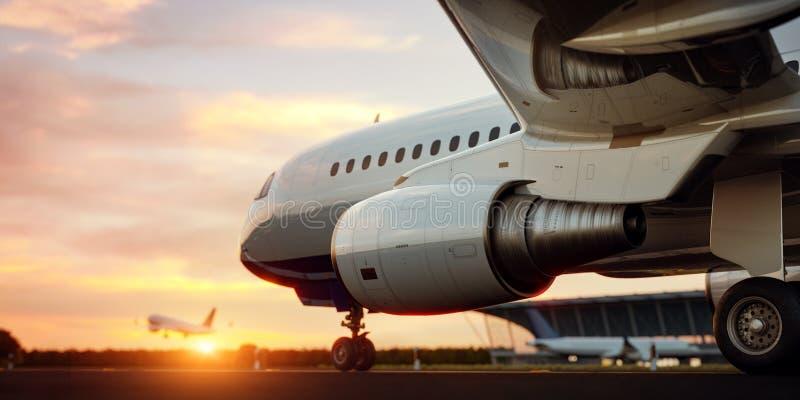 Aeroplano comercial blanco que se coloca en la pista del aeropuerto en la puesta del sol El aeroplano del pasajero est? sacando imagen de archivo libre de regalías