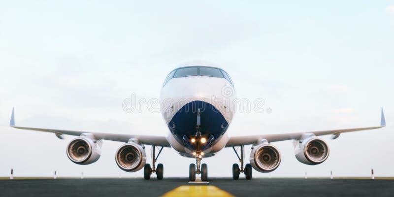 Aeroplano comercial blanco que se coloca en la pista del aeropuerto en la puesta del sol La vista delantera del aeroplano del pas imagenes de archivo