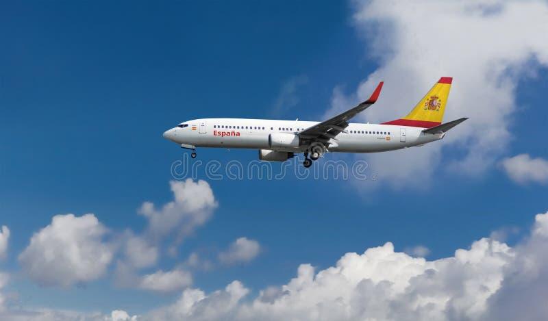 Aeroplano comercial con la bandera española en el aterrizaje de la cola y del fuselaje o el lanzamiento con el cielo nublado azul fotografía de archivo libre de regalías