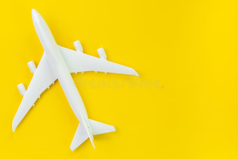 Aeroplano commerciale del giocattolo bianco su fondo giallo solido usando come carta da parati di affari del trasporto e di viagg immagine stock libera da diritti