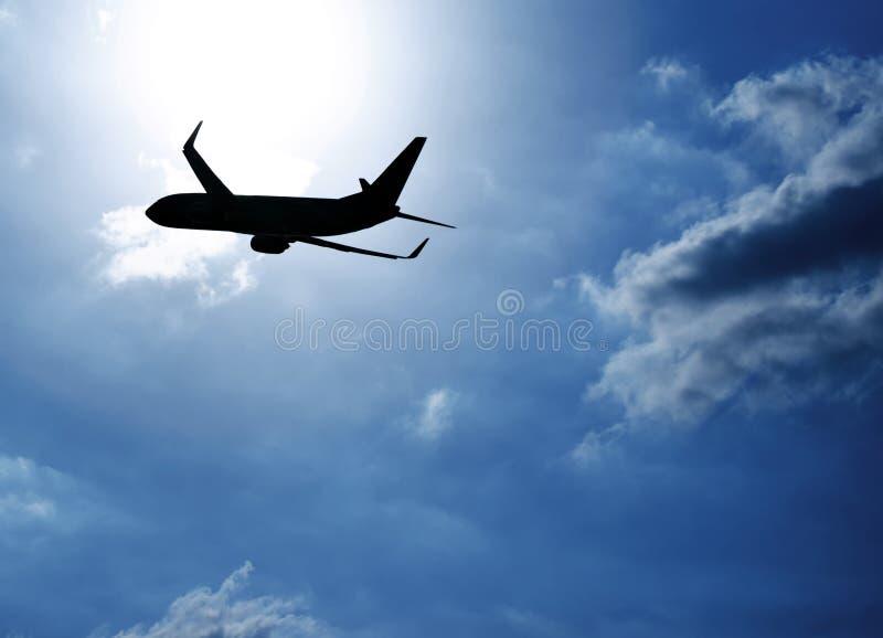 Aeroplano de la silueta en cielo azul foto de archivo