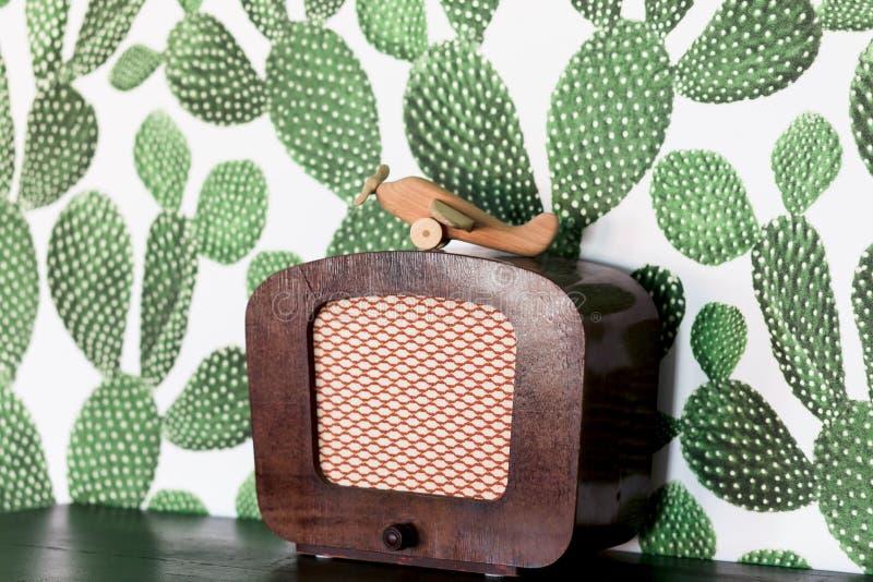 Aeroplano de madera retro del juguete en la tabla con el fondo del cactus fotos de archivo