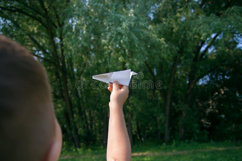 Aeroplano de papel en manos de los niños en fondo del verdor y cielo azul en día de verano soleado Concepto de verano, niñez, soñ foto de archivo