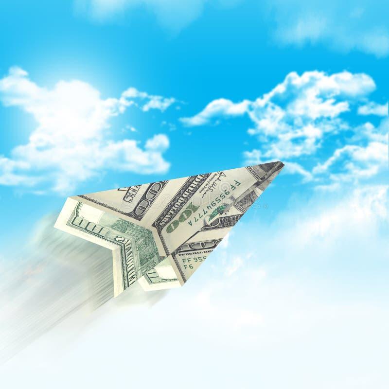 Aeroplano de papel hecho de cientos billetes de dólar imagenes de archivo