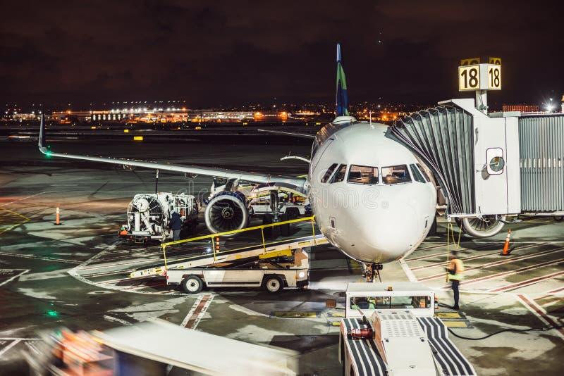 Aeroplano del pasajero en pista cerca del terminal en un aeropuerto en la noche Equipo de la tierra del aeropuerto que hace el se foto de archivo