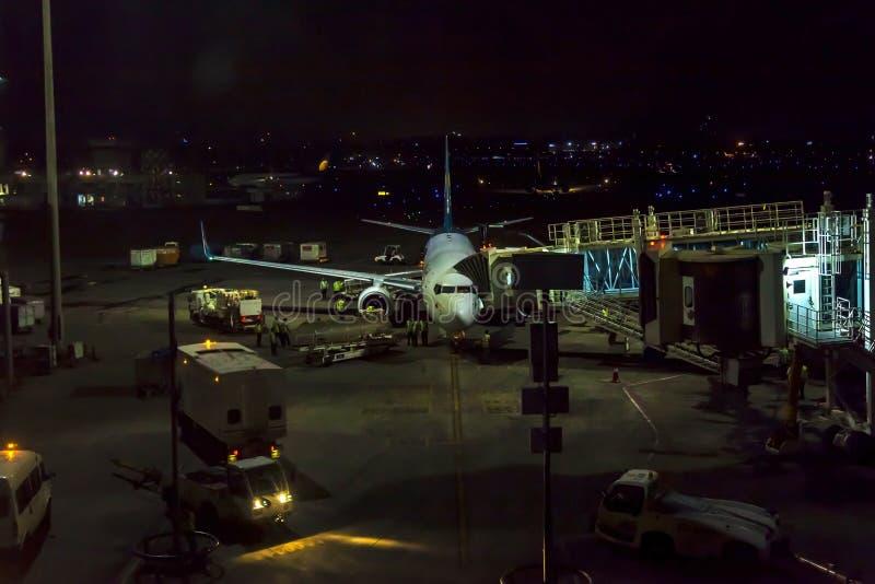 Aeroplano del pasajero en pista cerca del terminal en un aeropuerto en la noche Equipo de la tierra del aeropuerto que hace el se fotografía de archivo