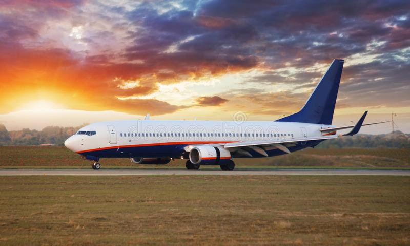 Aeroplano di atterraggio in aeroporto al tramonto fotografia stock
