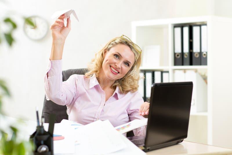 Aeroplano di carta di lancio della donna di affari in ufficio fotografia stock