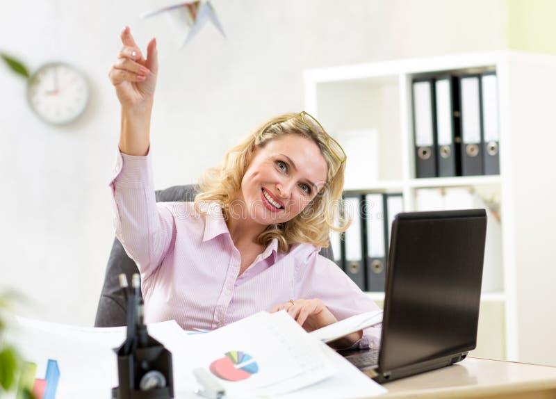 Aeroplano di carta di lancio della donna di affari in ufficio immagine stock libera da diritti