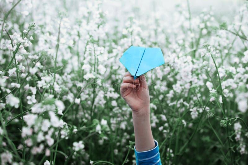 Aeroplano di carta in mani dei bambini su fondo bianco fotografia stock libera da diritti
