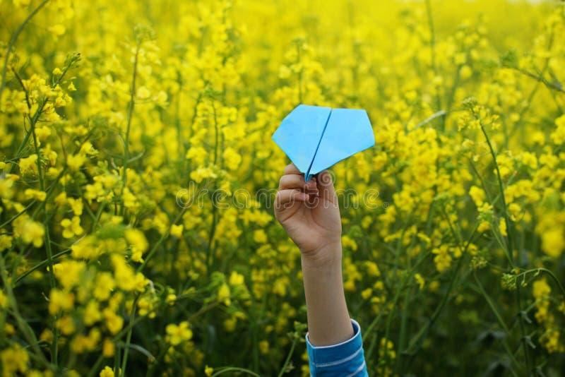 Aeroplano di carta in mani dei bambini su fondo giallo fotografie stock