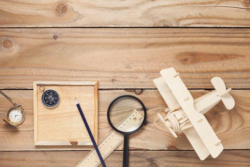 Aeroplano di legno, bussola, lente d'ingrandimento, orologio da tasca, righello e immagini stock