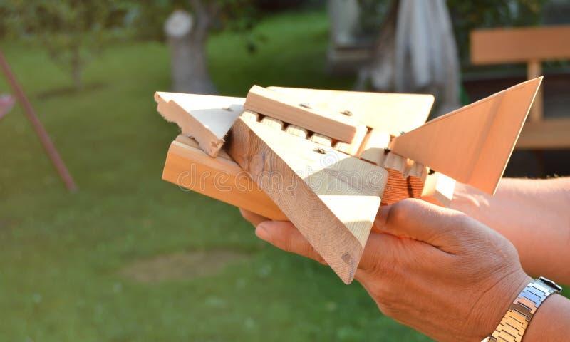 Aeroplano di legno casalingo nelle mani degli uomini, il concetto del giocattolo del viaggio, sogni, libertà, giocante con il bam fotografie stock libere da diritti