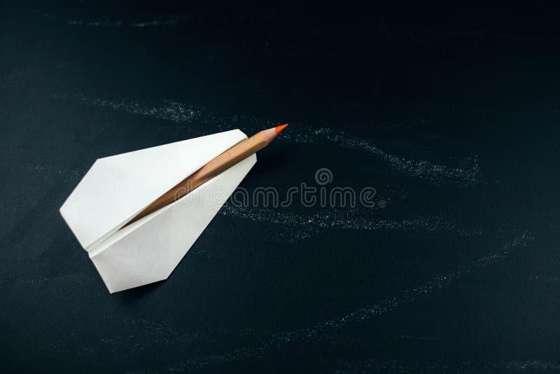Aeroplano di Libro Bianco con il pastello sulla lavagna nera fotografie stock libere da diritti