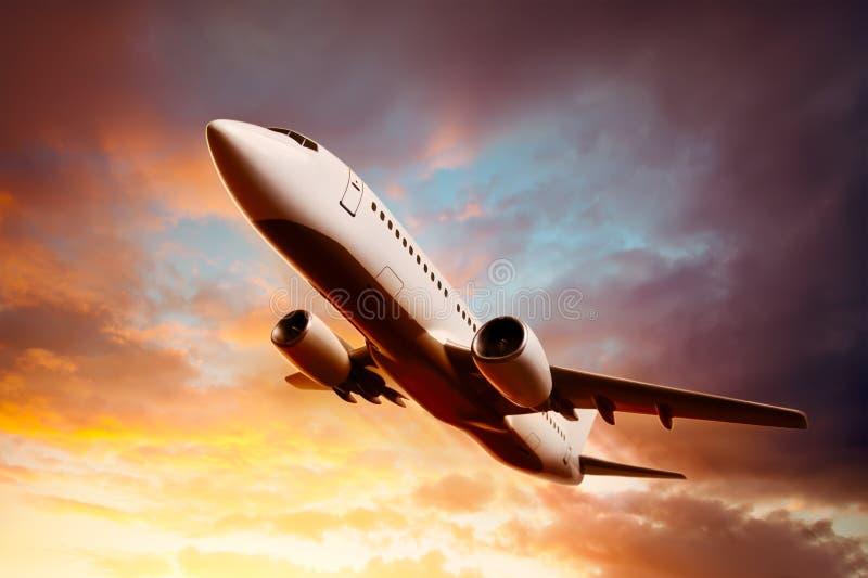 Aeroplano en el cielo en la puesta del sol imagen de archivo libre de regalías