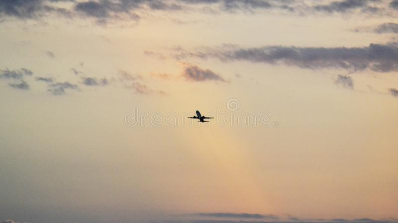 Aeroplano en el fondo del cielo Despegue del aeroplano en cielo de la puesta del sol fotografía de archivo