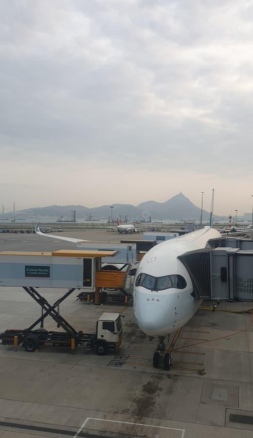 Aeroplano en el terminal de Hong Kong que es cargado con equipaje imagen de archivo