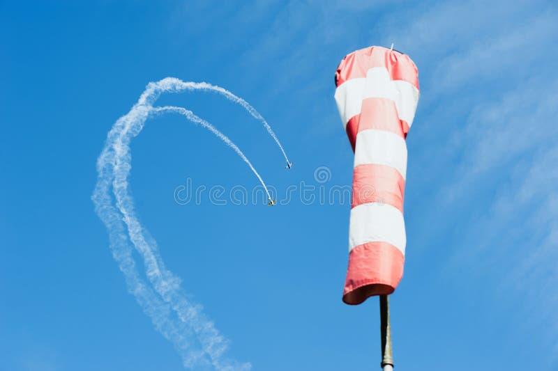 Aeroplano monomotore due nel tiraggio del cielo un ciclo dalle nuvole sulla direzione del vento del fondo immagini stock