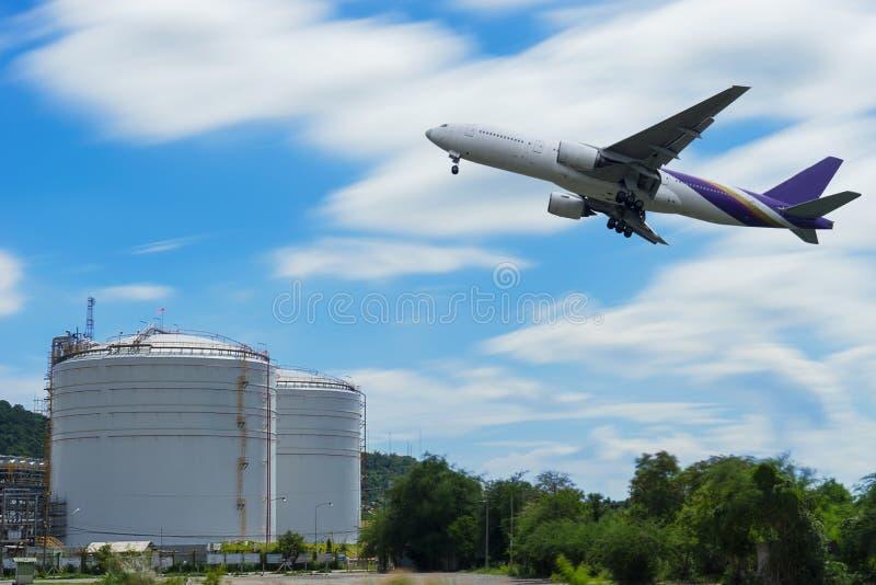 Aeroplano nel cielo sopra i serbatoi alla stazione di servizio con il blu fotografia stock