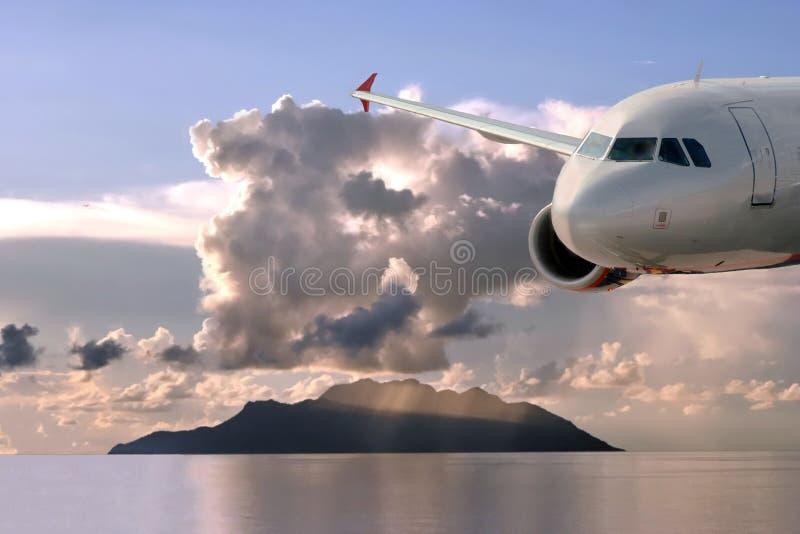 Aeroplano, nubi, isola, mare   fotografia stock libera da diritti