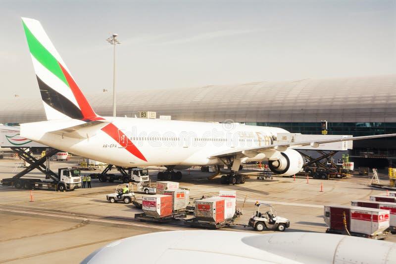 Aeroplano parqueado en el muelle del aeropuerto internacional de Dubai, las mercancías cargadas y la preparación antes del vuelo foto de archivo libre de regalías