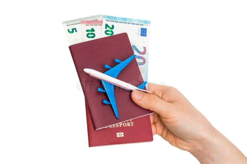 Aeroplano, pasaporte y dinero en la mano femenina - concepto que viaja fotos de archivo libres de regalías