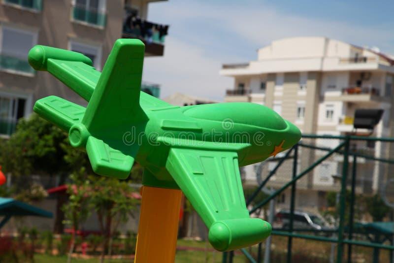 Aeroplano plástico verde en el patio fotos de archivo