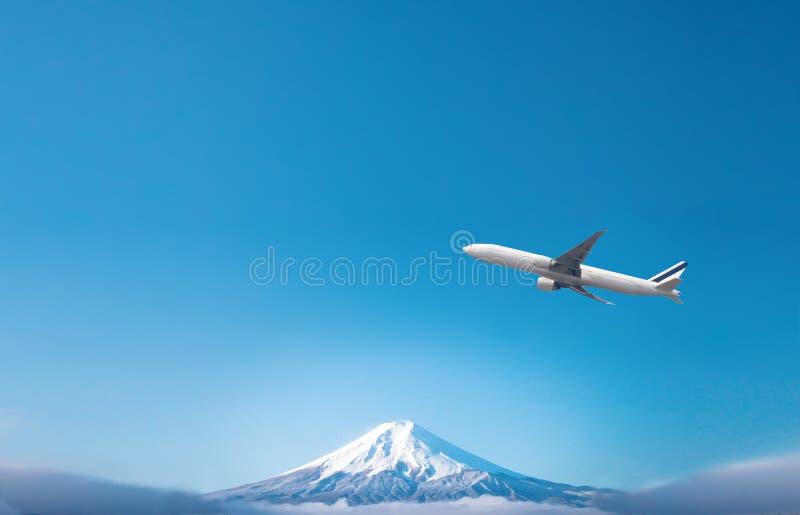 Aeroplano que fríe sobre el fondo de Fuji de la montaña de la nieve vista del Fuji-san, la montaña más alta de Japón foto de archivo
